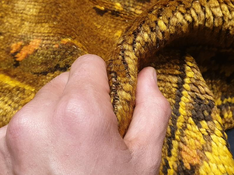 A hand holding the rug showing stitches of it. They are known with their soft & shiny texture